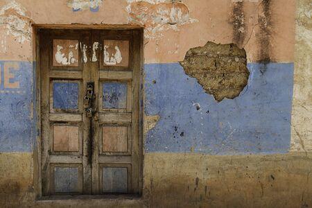 porte bois: ancienne porte vintage dans un mur wheatered ferm�e avec quatre verrous