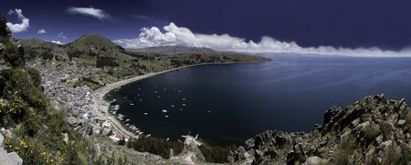 titicaca lake high altitude in andes between Bolivia and Peru city of Copacabana near isla del sol and Isla de la luna sunny day with nice white clouds in blue sky and water panorama with copy space photo
