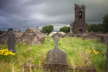 Irish graveyard at Dingle peninsula old ruins of church long exposure gives moody feel caused by blurry vegetation and clouds photo