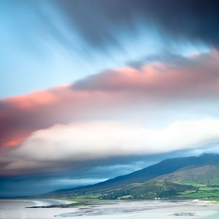 dark clouds during sunset over Irish coast Dingle peninsula Kerry district hills and beach long exposure image give a dramatic look photo