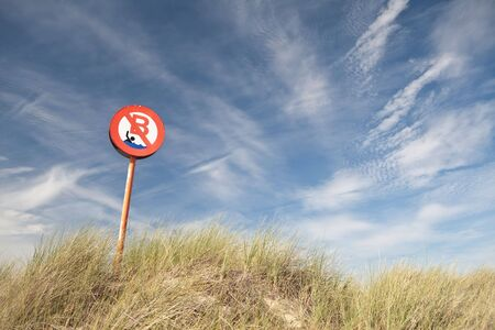no bathing or swimming  sign in the dunes long grass blue sky white clouds background with copy space photo