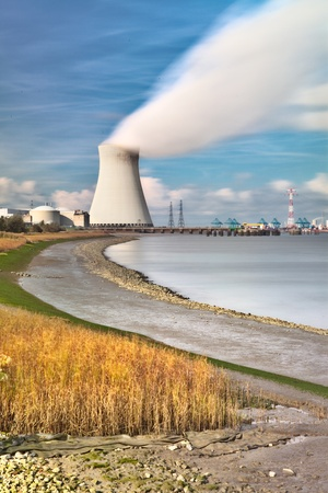 cooling towers of a nuclear power plant creating clouds in the Antwerp harbor photo