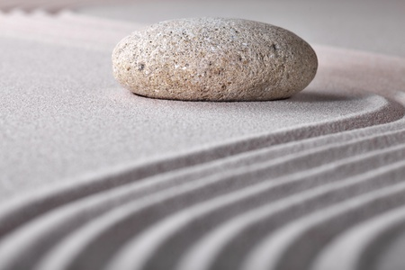 stone sand zen garden raked sand and pebble abstract for balance calmness spiritual and tranquil rippled pattern trxture and lines background photo