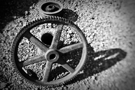 mine site: old cog wheel at abandoned 19the century mine site in sardinia Italy, artistic image monochrome and with tilt shift lens