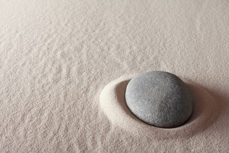 zen meditation stone relaxation or concentration point to focus and to meditate round grey rock in sand simplicity and purity spa background Stock Photo - 13222530