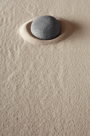 zen meditation stone relaxation or concentration point to focus and to meditate round grey rock in dry sand simplicity and purity spa background abstract concept photo