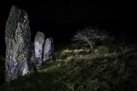 megalith: Three standing stones at Cloghan, Dingle peninsula, Kerry Distric Ireland. Megalith of Celtic stone age at night under a clear sky. Mystical menhir monument of prehistoric era and old culture. Landscape lightpainting