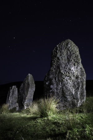 ���stone age���: Three standing stones at Cloghan, Dingle peninsula, Kerry Distric Ireland. Megalith of Celtic stone age at night under a clear sky. Mystical menhir monument of prehistoric era and old culture. Landscape lightpainting