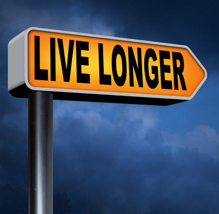 longer: live long road sign. A healthy lifestyle helps to to have a longer life in good health. Living stressfree and relaxed Stock Photo
