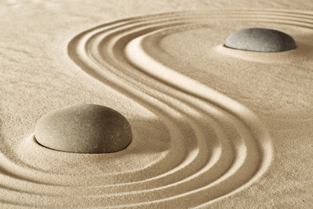 zen stones or rocks and raked lines in sand Japanese stone garden for meditation. Purity balance and spirituality background. Spa wellness massage rock therapy Standard-Bild