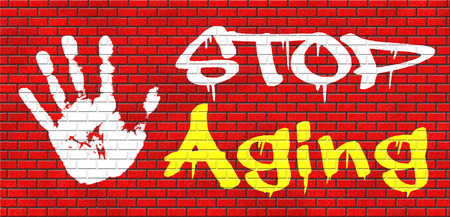 anti ageing: stop aging stay young forever staying and looking younger than you are not growing old grafitty on red brick wall, text and hand