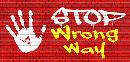 wrong way: wrong way stop and take a uturn making a mistake turn back now bad direction grafitty on red brick wall, text and hand