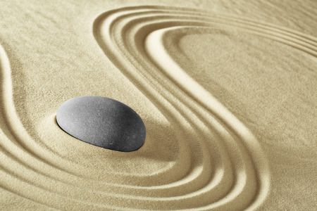 massage stone: Spa wellnees background massage stone treatment and therapy. Purity serenity harmony and balance in round rock and lines in the sand. Stock Photo