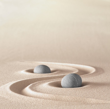 and harmony: zen garden meditation stone background with copy space stones and lines in sand for relaxation balance and harmony spirituality or spa wellness