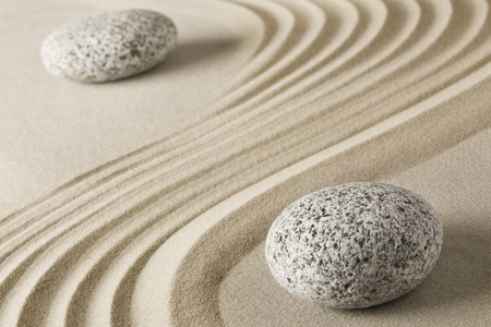 Yin and yang  Chinese Tao philosophy. Stones and sand pattern. Round rocks stand for Ying and jang in zen stone garden. Stok Fotoğraf - 74429903