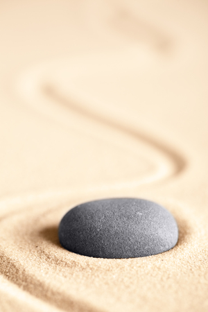 Round rock on textured sand background with room for copy space.