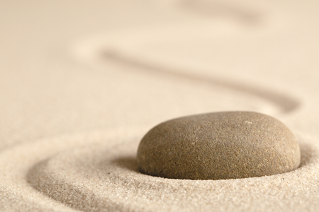 Zen meditation stone with raked line in sand. Concept for harmony relaxation and purity. Фото со стока