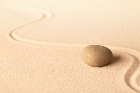 Concentration trough focus on a zen meditation stone. Round rock in sand texture background. Concept for yoga or spa welness treatment. Standard-Bild - 119667831