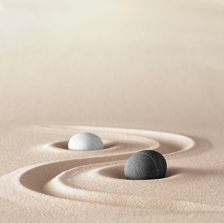 yin and Yang symbol of dualism in ancient Chinese philosophy where opposite or contrary forces are complementary. Like light and dark or fire and water, male and female. A black and a white round stone vonvept jin jang. Archivio Fotografico