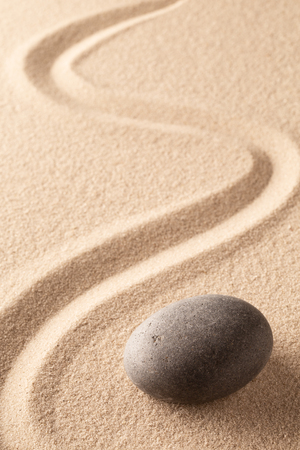 curved line in the sand of a zen stone garden. A round black rock on sandy background. Concept for spirituality, harmony and balance. Standard-Bild - 119668002