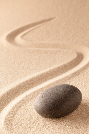black round zen meditation stone for focus and concentration in Japanese sand garden. Textured background with copy space for mindfulness or spa wellness. Standard-Bild - 119668003