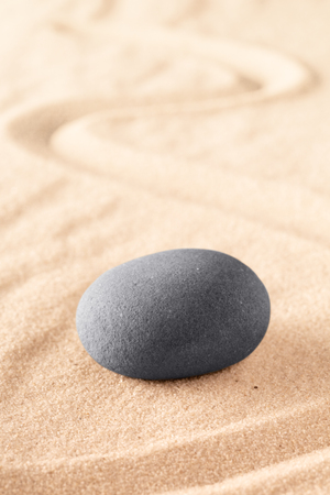 round stone on sand with line. Zen meditation or spa wellness background. Japanese sandy garden. Фото со стока