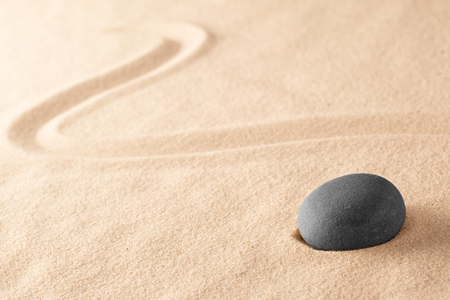 black zen meditation stone in Japanese sand garden. Concept for harmony and balance in yoga and mindfulness. Standard-Bild - 121959690