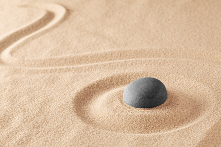 Mineral stone therapy for a quiet peace of mind through zen meditation and relaxation. Spa wellness or reiki spiritual healing of mind body and soul, mindfulness. Raked sand background with teture and copy space.