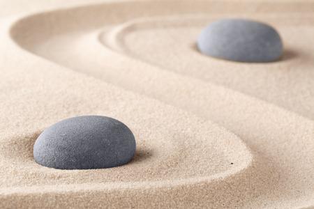 Zen-Garten-Meditationsstein. Runder Felsen auf sandigem Beschaffenheitshintergrund. Yoga- oder Achtsamkeitskonzept.