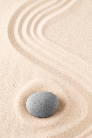 Piedra de meditación del jardín zen. Roca redonda sobre fondo de textura arenosa. Concepto de yoga o atención plena.