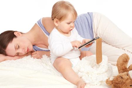 madre soltera: Ni�o que juega con su smartphone mientras que la madre est� durmiendo