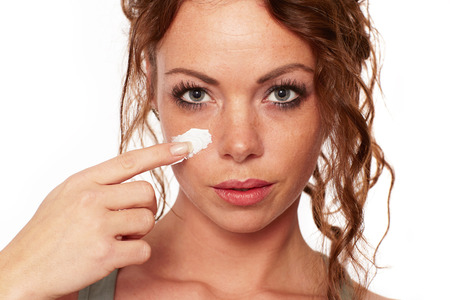 commonplace: Woman with natural skin applies a face cream