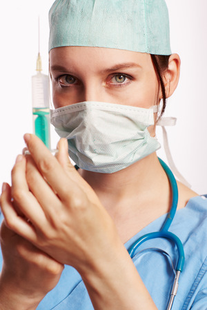 physican: Nurse in blue dress with Op stethoscope and syringe as Cut . Stock Photo