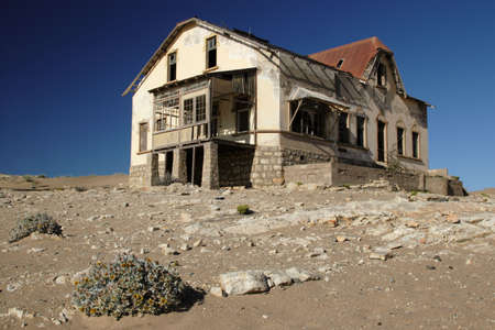 Deserted house in the abandoned diamond digging town Kolmanskop, Namibia photo