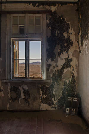 View into the desert out of an abandoned house in the ghost town Kolmanskop, Namibia photo
