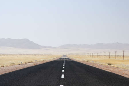 a mirage: Lonely desert road in Namibia with heat mirage over the horizon