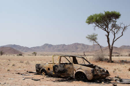 burnt out: Burnt out car wreck at the roadside in the Namibian Desert Stock Photo