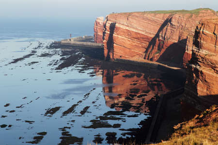 Cliff line of Heligoland in early morning light with reflection in the water. photo