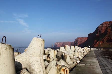 Cliff coast of Helgoland, in the background the famous Tall Anna, in the foreground Tetrapods as coast protection. photo