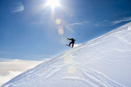 Snowboarder jumps down an incline of the Mountain on a bright, sunny day with blue skies. Stock Photo