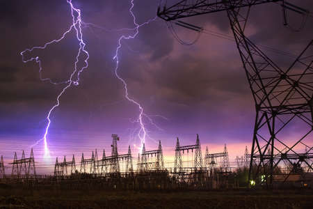 번개를 타오르는 전기 타워와 전원 배포 역의 극적인 이미지. 스톡 콘텐츠