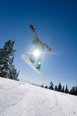 男性のスノーボーダーは明るい晴れた日に大きな空気をキャッチします。