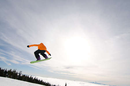 snowboarder jumping: Male Snowboarder Catches Big Air on a Bright Sunny Day.