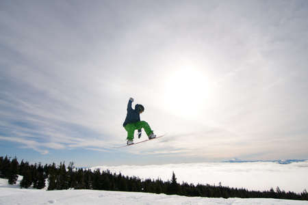 Male Snowboarder Catches Big Air on a Bright Sunny Day. photo