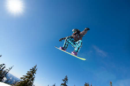 Male Snowboarder Catches Big Air on a Bright Sunny Day. Фото со стока - 9054356