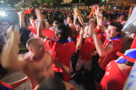 cheering fans: RIO DE JANEIRO - JUNE 18: A crowd of Chilean Fans celebrate Chiles victory over Spain.