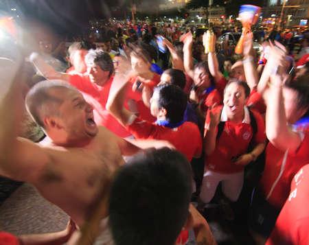 color fan: RIO DE JANEIRO - JUNE 18: A crowd of Chilean Fans celebrate Chiles victory over Spain.