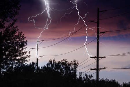 struck: Silhouette of Power Lines being struck by lightning. Stock Photo