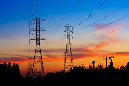 on high: Hermosa silueta de Torres de electricidad durante la puesta del sol. Foto de archivo