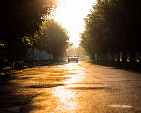 Road with lonely car. Red sunset light and high contrast. Stockfoto